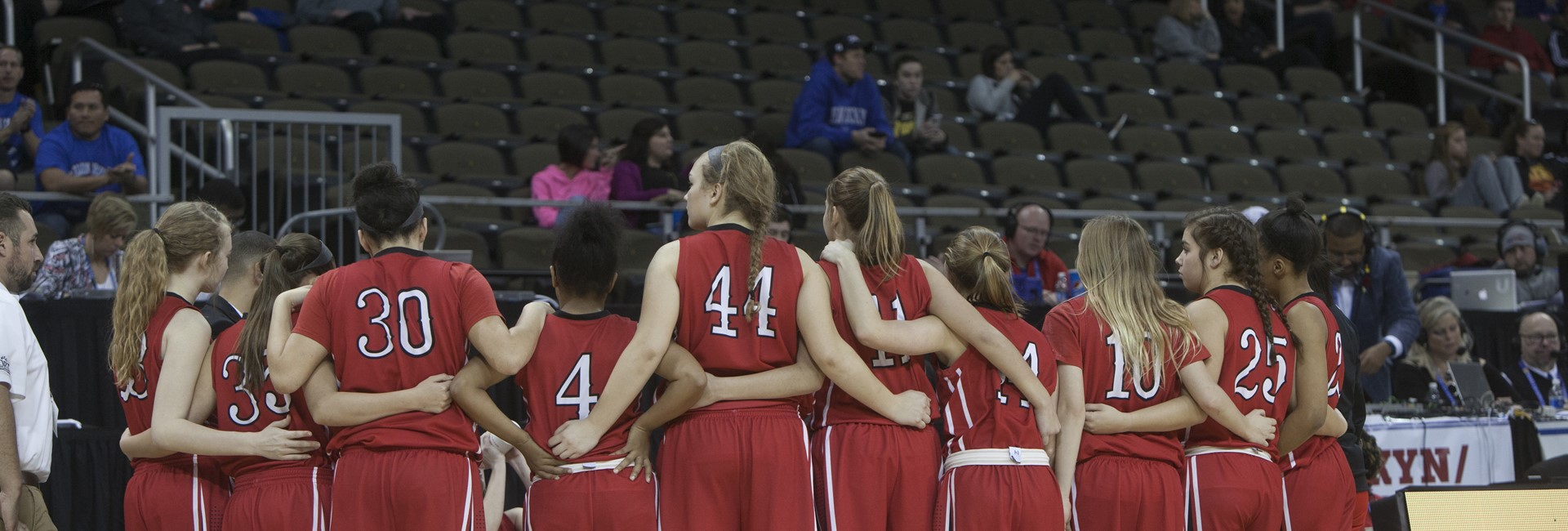Lady Cards huddle during Sweet 16 basketball contest.