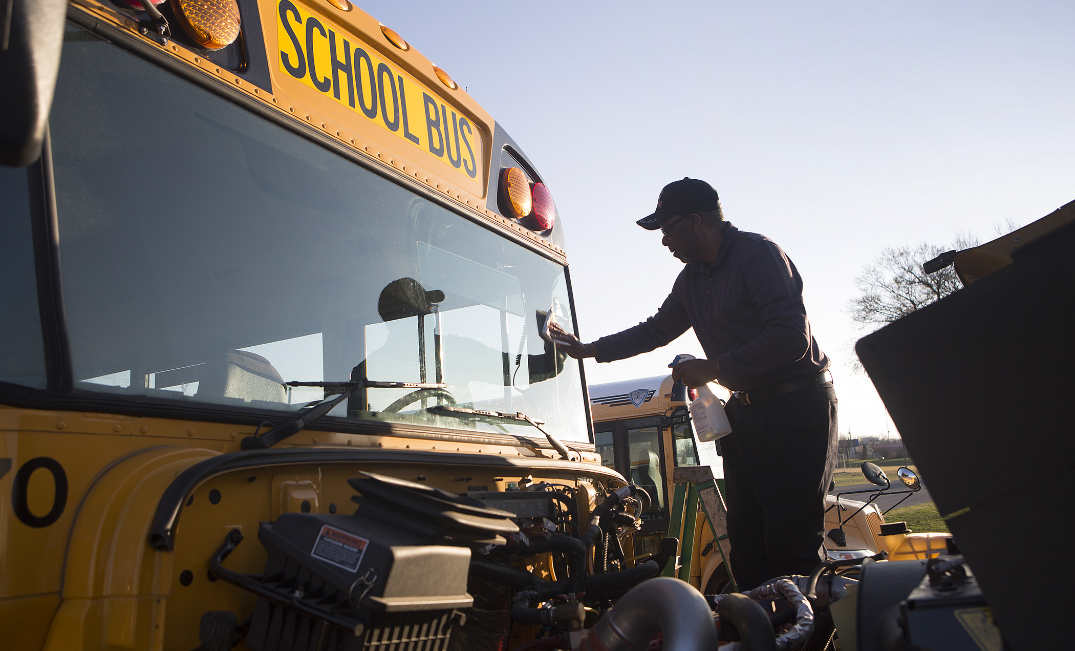 Nelson County Schools bus driver Jewel Brock cleans his windshield following his morning bus route.